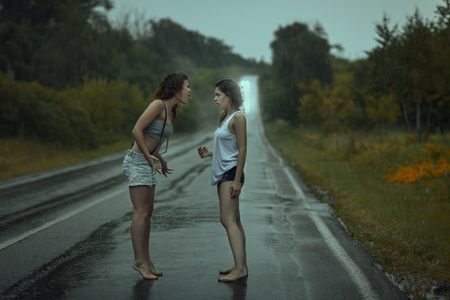 freaking: Young cirls quarrel to sort things out on the road in the rain