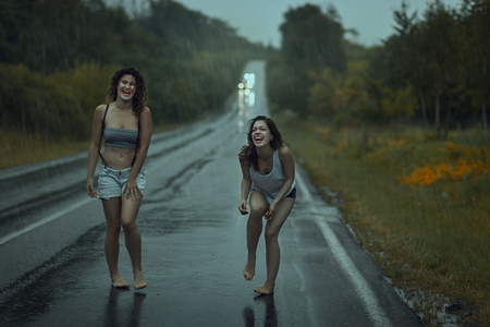 mirth: Teen girls laughing on the road in the rain