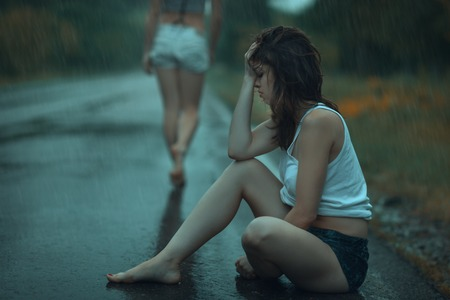 malice: A young sad  girl sitting on the road in the rain Stock Photo