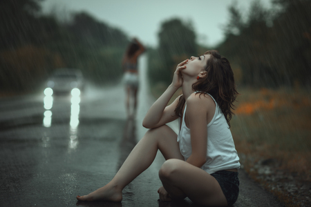 Woman in the rain and sad, from her friend had gone. Stock Photo