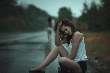 freaking: A young sad  girl crying sitting on the road in the rain