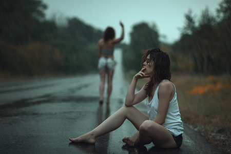 A young sad  girl  sitting on the road in the rain