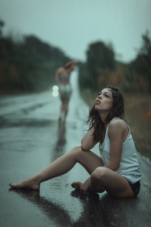 A young girl crying sitting on the road in the rain Stock Photo