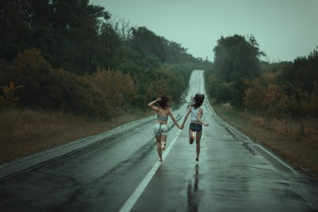 soppy: Young girls runing on the road in the rain