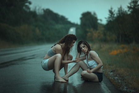 A couple of young girls sitting on the road in the rain