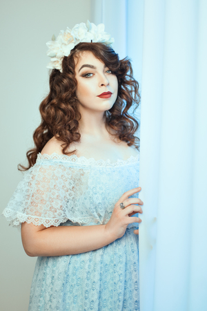 buxom: Gentle young woman standing near a window holding a curtain. Soft focus with small depth of field. Stock Photo