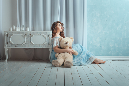 sightly: Beautiful woman with overweight sitting on the floor in the room. In her hands she holds toy bear. Stock Photo