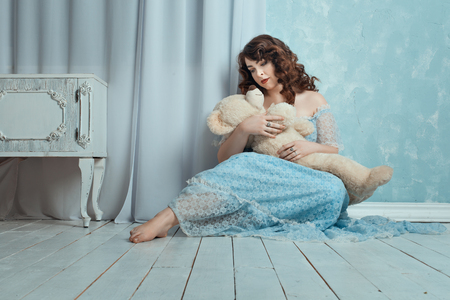 sightly: Woman sitting on the floor in the room, on the hands is a toy bear. Stock Photo