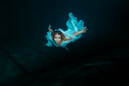 profound: A woman in a white dress as a mermaid swimming under water.