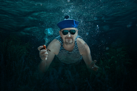 Man swimming underwater sailor and smokes a pipe.