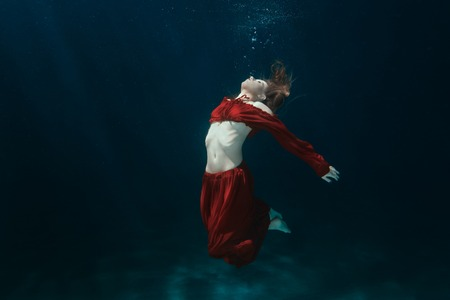 profound: Woman in a red dress on the bottom underwater.