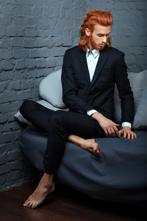 metrosexual: Red-haired man in a business suit sitting on the couch, he is metrosexual.
