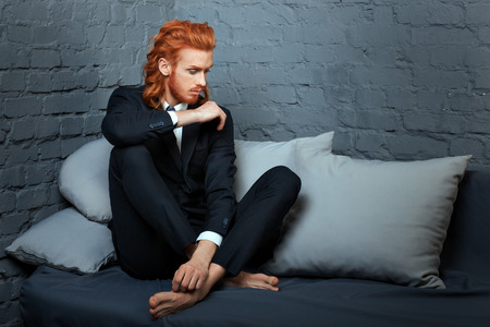metrosexual: Metrosexual man with red hair and a beard sitting on a couch.