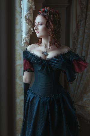 Woman in Victorian dress standing at the window. Banco de Imagens