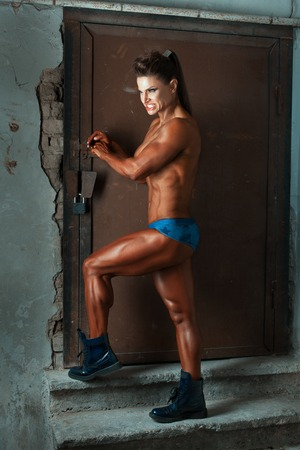 wicked: Bronze woman bodybuilder with a wicked facial expressions.