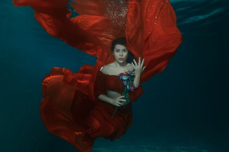 Woman in a red dress under water, in the hands holding flowers. Stock Photo