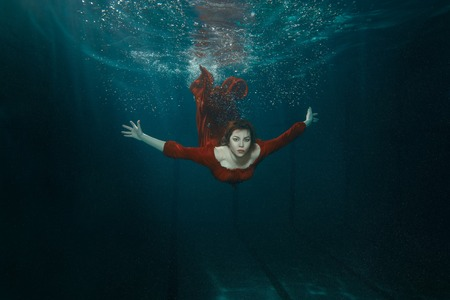 Woman in a red dress swimming under water deeply.