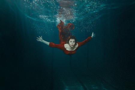 깊은 물 아래 빨간 드레스 수영 여자.