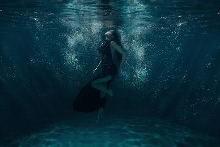 Meisje op de oceaanbodem onder de lichtstralen die door het water.