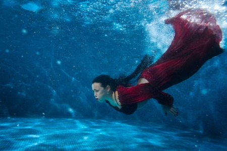 Woman in red dress dives under water in the pool. Stok Fotoğraf