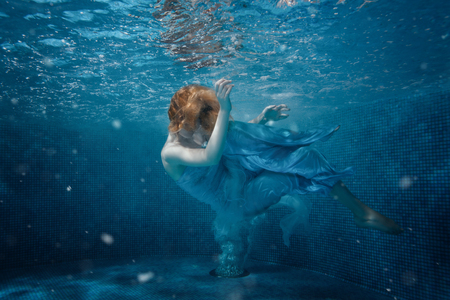 profound: Girl in blue dress under water in the pool.