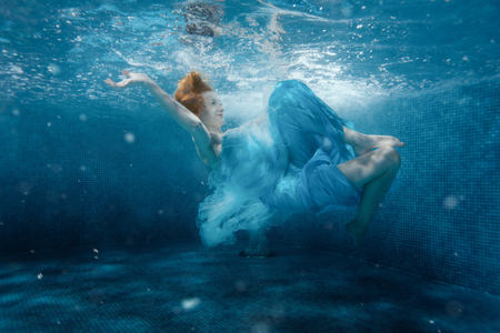 The girl from the fairy tale flounders in a blue dress under water. Stock Photo