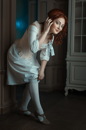 domestics: Girl flirtatiously straightens stockings on her feet, she was in the Renaissance style. Stock Photo