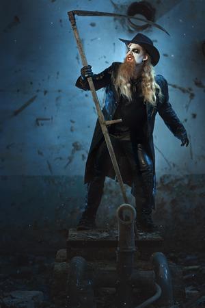 imminence: Hombre con una cara de pie enojado que sostiene una guadaña en la mano, esto sugiere el horror y el miedo.