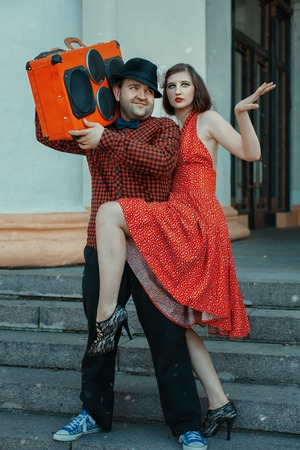 Man holding a musical installing, close dancing woman, retro style.