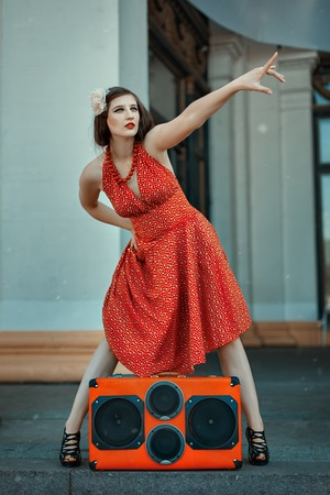 humorously: Woman dancer pointing her finger near the music system.