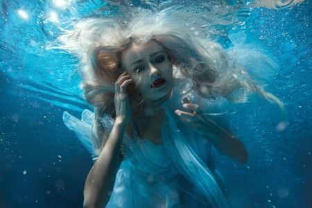 Up portrait of a girl under the water.