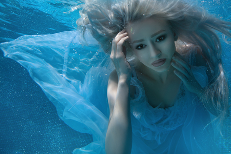 Blonde woman under water, her long hair and a white dress. Stock Photo