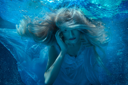 Fabulous blonde woman under water, her long hair and a white dress.