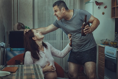 social problems: Alcoholic husband beats his wife, at home in the kitchen. Social problems of the family.