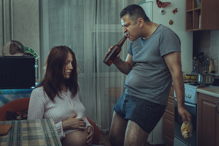 fracas: Kitchen sits sad and depressed woman near a drunken husband. Social problems of the family. Stock Photo