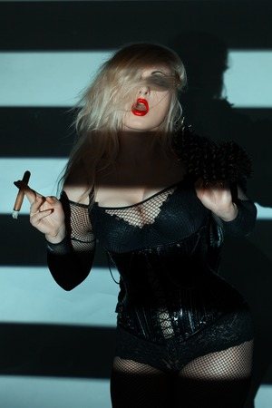 Vulgar woman with red lips, she was holding a fat cigar.