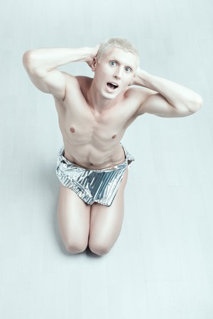 womanlike: Man albino sits on the floor and screaming, his eyes crazy.