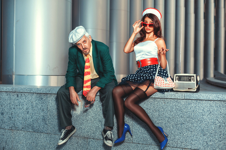 humorously: Old man with a young woman in retro style.