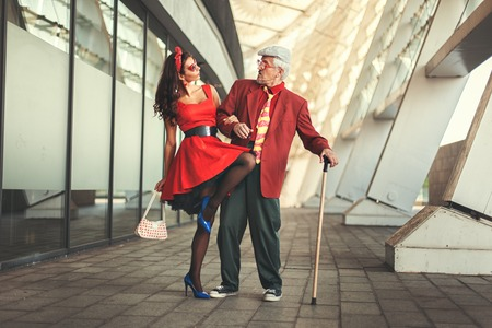 humorously: Old man dancing with a young girl, they dressed in retro. Stock Photo