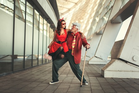 humorously: Young girl is dancing with the old man, they are dressed in retro clothes.