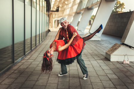 humorously: woman in dance has jumped on the old man, they in a retro garb.