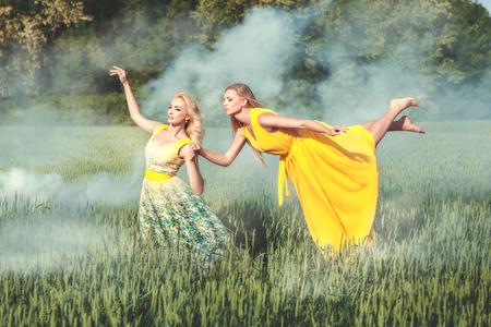 Sobre un campo de humo blanco. Mujer que vuela sobre el campo, la segunda mujer es la celebración de su mano.