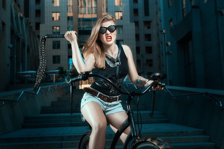 attractive charismatic: Woman with a whip in biker style on the bike, she aggressive.