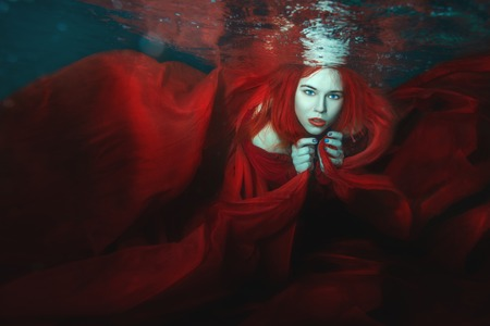 arise: Woman in a red dress swimming under water.