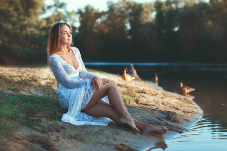 Woman in white dress sitting by the lake in the woods.