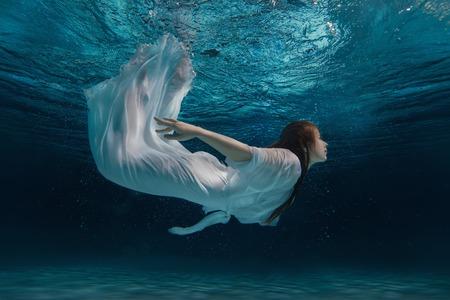 Mujer en la natación vestido blanco bajo el agua como una sirena en medio de ráfagas.