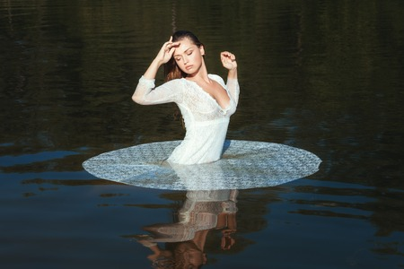 Woman in white openwork dress standing in the lake in the nature. Фото со стока