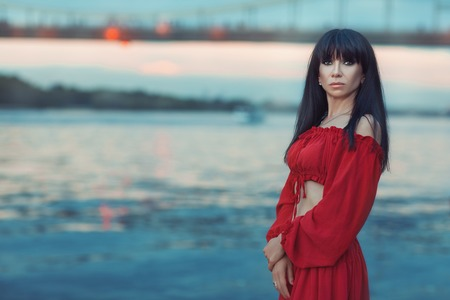 Portrait of a woman in a red dress on the river bank at sunset. Stock Photo