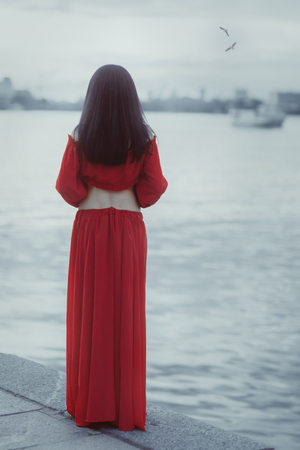 Woman stands on the shore of the sea and waiting. Stock Photo