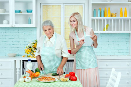 taught: Grandma taught to cook a young girl in the kitchen. Stock Photo